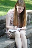Emma Sue Writing in WW park Senior Picture