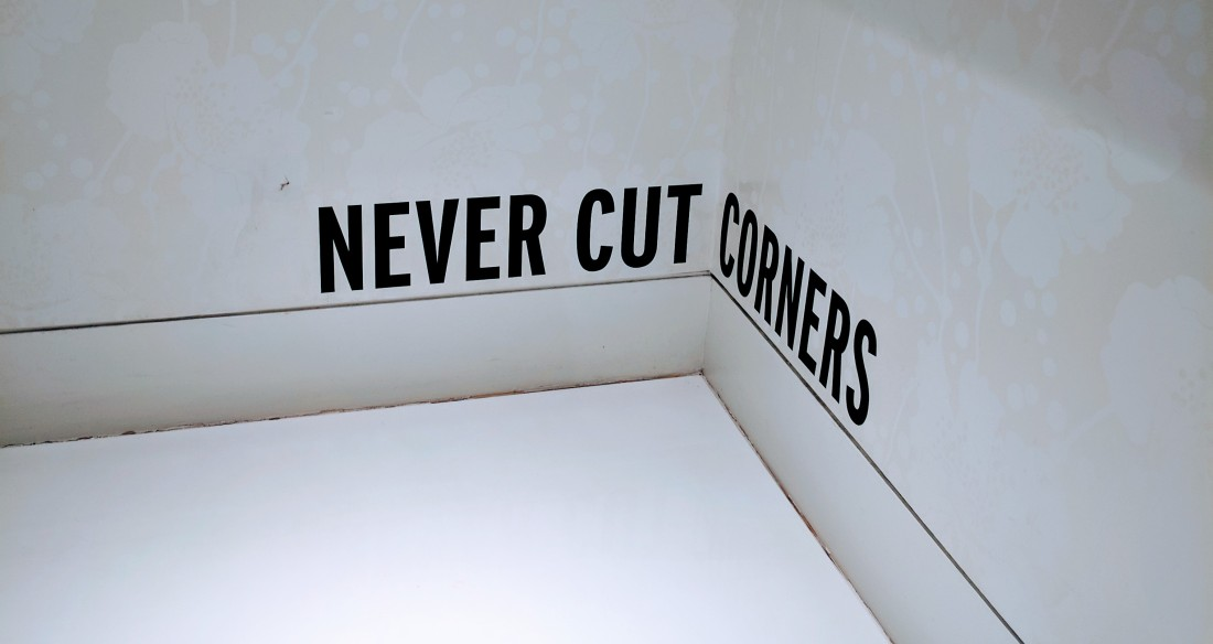"""Sign in Kate Spade New York store reading """"never cut corners."""""""
