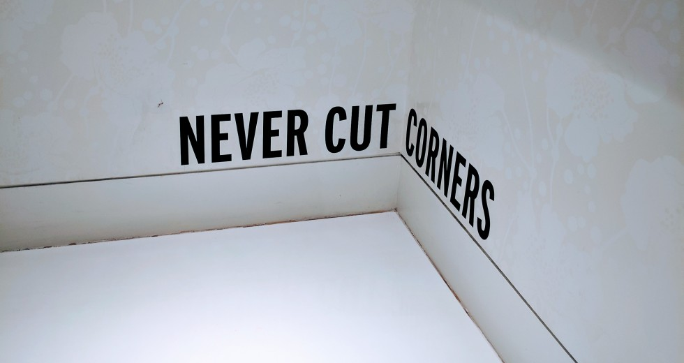 "Sign in Kate Spade New York store reading ""never cut corners."""